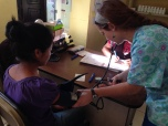 Katie taking a patient's blood pressure as part of the triage process at the clinic