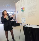 Alex Costa Explains her Senior Symposium Poster. Courtesy of Ferris State University's SmugMug.