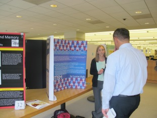 Lauren Kelly explains her Senior Symposium poster. Courtesy of the Honors Program at Ferris University,